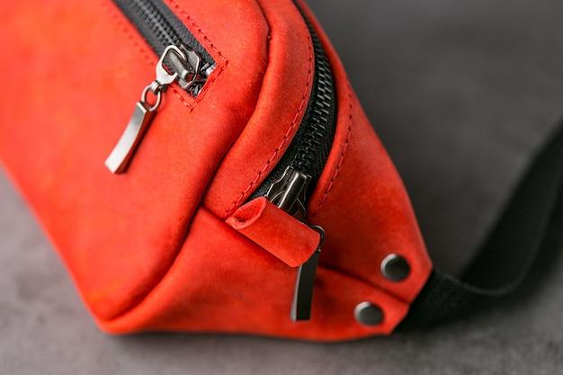 회색 가죽으로 만든 빨간 허리 가방