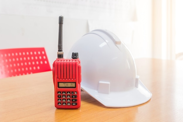 Red walkie-talkie radio and a white safety helmet on wooden background