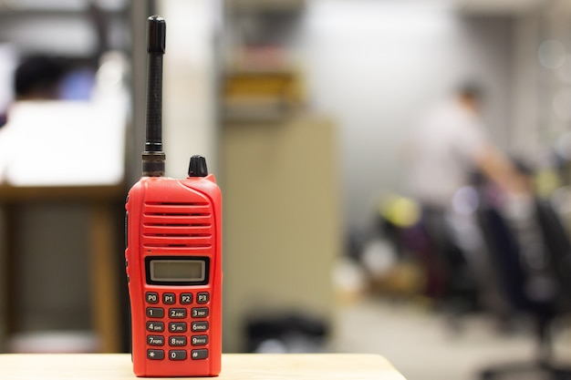 Red walkie-talkie radio on wooden table operator in office