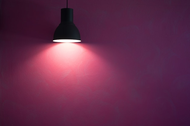 Red wall illuminated by vintage black stylish cone lamp.
