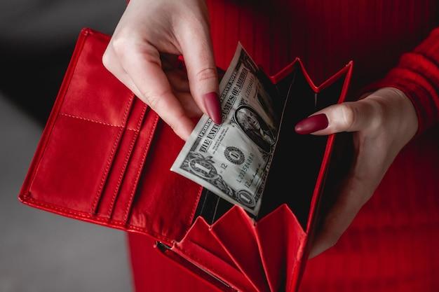 Красный кошелек в руках женщины в красном платье с красным маникюром