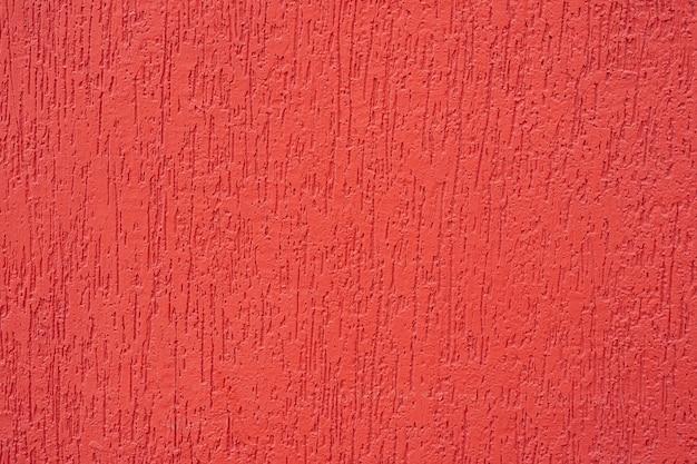 赤い壁、テクスチャ、背景。セメントの壁に描かれた赤いブラシの美しい質感