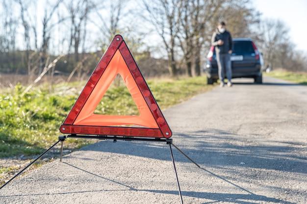 壊れた車の前の道路上の赤い警告トライアングル