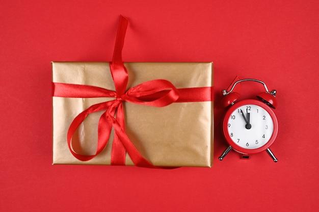 빨간색 배경에 빨간색 시계와 선물 포장. 고품질 사진
