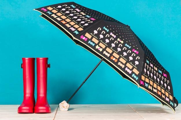 オープン傘の横に赤い水のブーツ Premium写真
