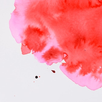 Red watercolor paint flowing on white background