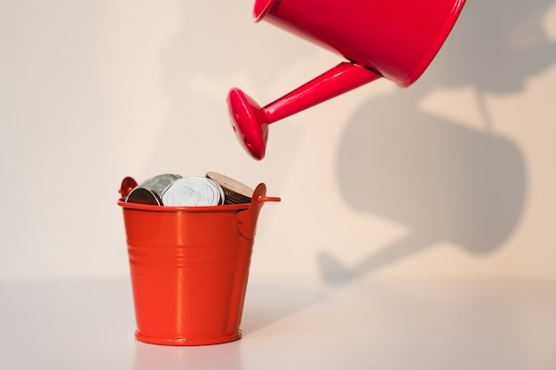 Red watering can with red bucket contain coins