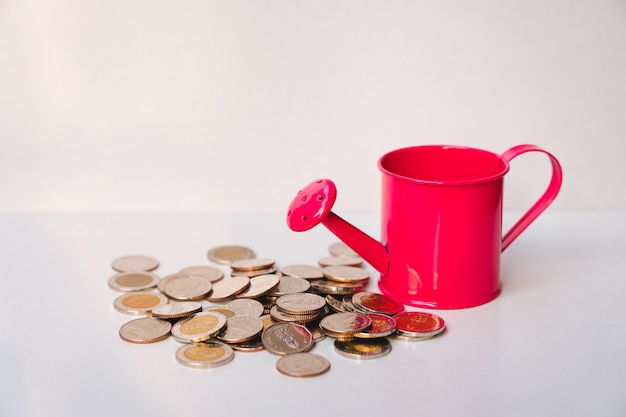 Red watering can with stack coins