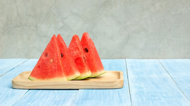 Red watermelon on a plate and blue wooden table.
