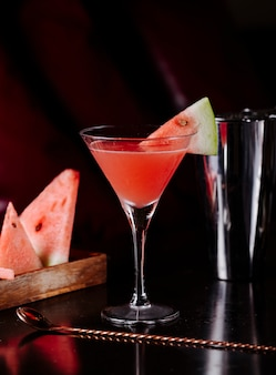 Red watermelon syrup cosmopolitan and fruit slices.