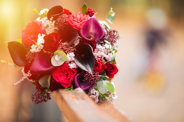 Red, wedding bouquet. lies on a wooden bench in the park
