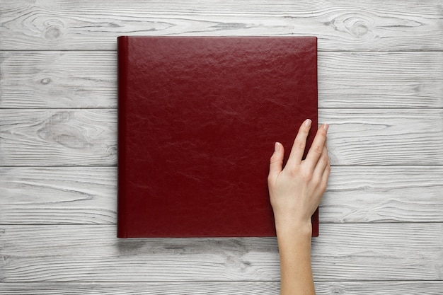 Red wedding photo book with  leather cover.  stylish wedding photo album close up. person opens a square photobook. family burgundy photoalbum on the table. womans hand holding a family photo album