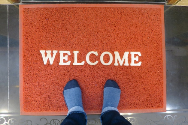 A red welcome doormat with feet wearing socks. interior and object concept.