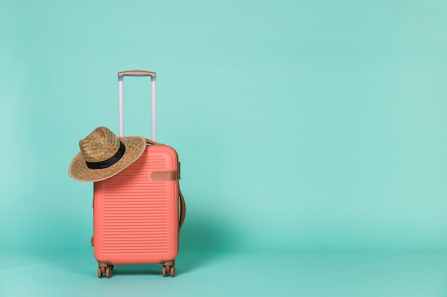 Red wheeled suitcase with hat