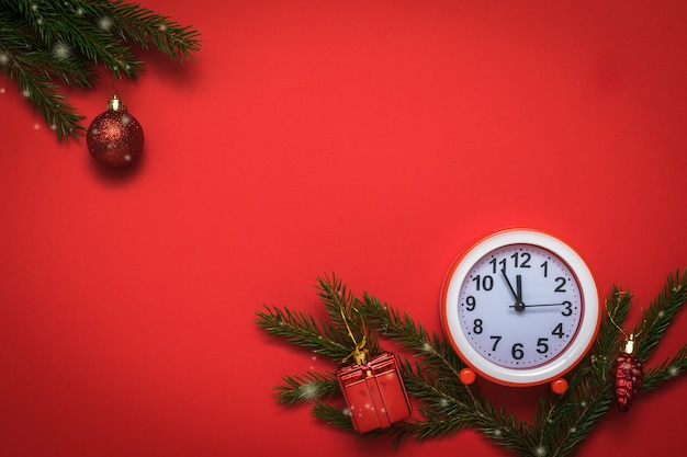 Red and white alarm clock, spruce branches and decorations on a red background.