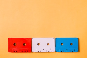 Red; white and blue cassette tapes on colored background