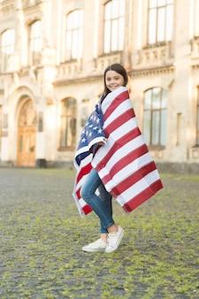 Красный, белый и синий я для тебя. счастливая девушка носит американский флаг. американский ребенок празднует день флага. государственный флаг сша. день независимости. 4 июля. гордость и достоинство. ты великий старый флаг.