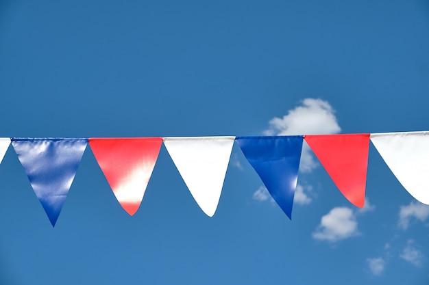 하늘 배경에 빨간색 흰색과 파란색 삼각형 깃발 천