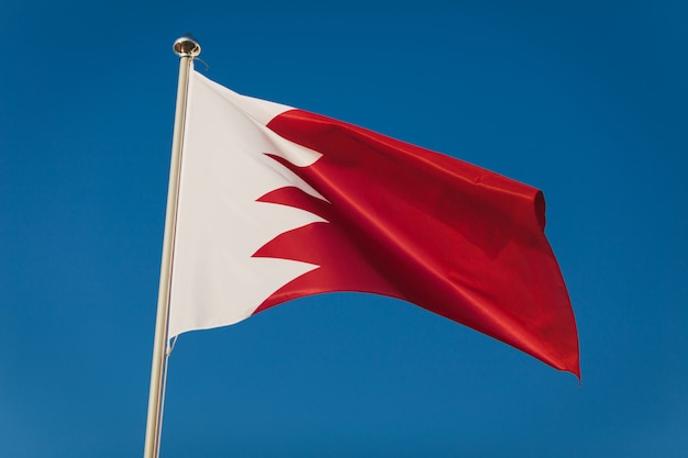 Red and white bahrain flag, capital manama. national flag on flagpole in front of blue sky