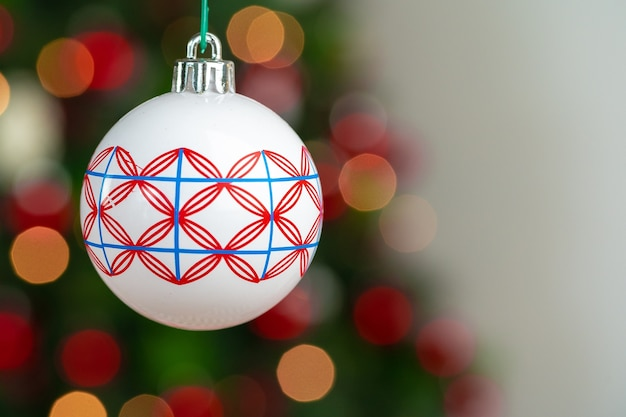 Red and white bauble hanging from a christmas tree