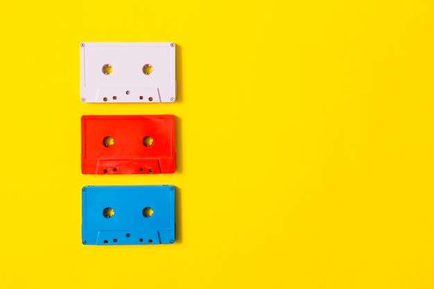 Red; white and blue audio cassette tape on yellow background