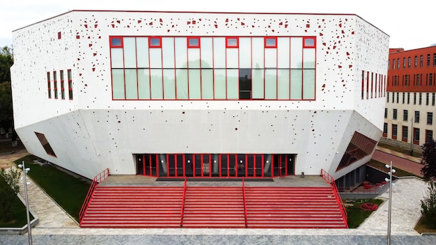 A red - white building with modern view and stairs in front of it in bucharest, romania