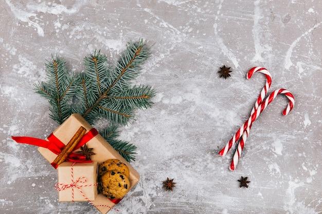 Caramelle bianche rosse, ramo di abete, scatola e biscotti sul pavimento grigio