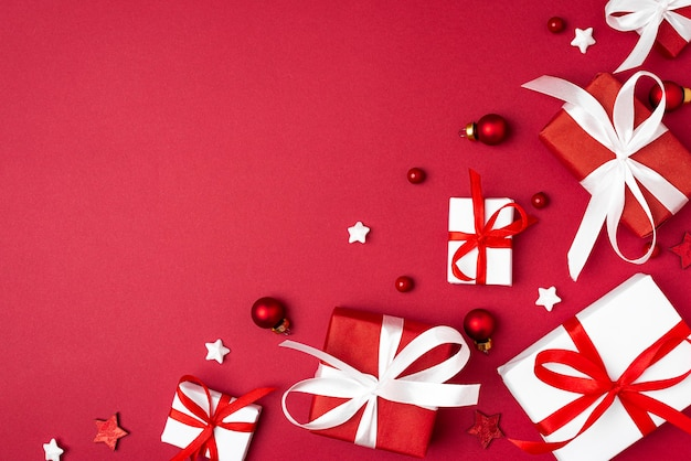 Red and white christmas gift boxes on red background