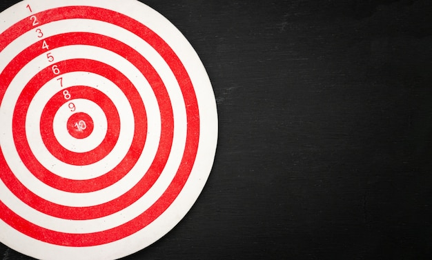Red and white dartboard filled with wrinkles on a black wooden background.