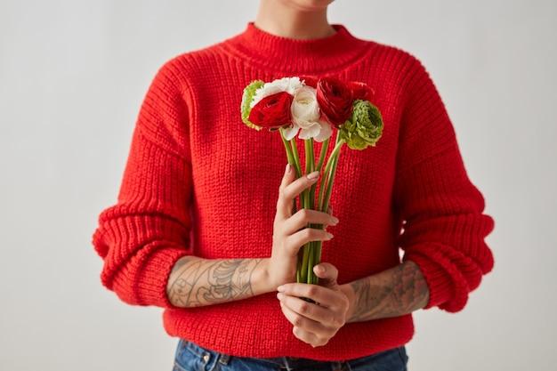 빨간색, 흰색, 녹색 꽃 라넌큘러스는 회색 배경에 문신이 있는 소녀를 안고 있습니다. 어머니의 날 엽서