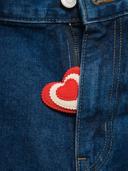 Red and white heart sticking out of the open fly blue jeans.