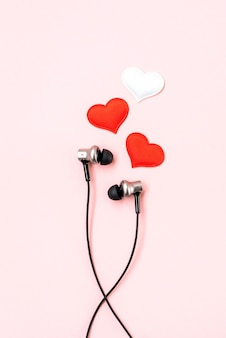 Red and white hearts with black earphones on pink pastel.