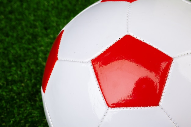 Red and white leather soccer ball, close up