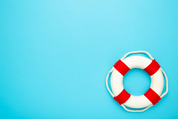 Red-white lifebuoy on blue background. copy space