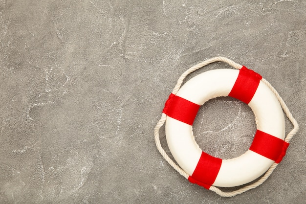 Red-white lifebuoy on grey concrete background with copy space