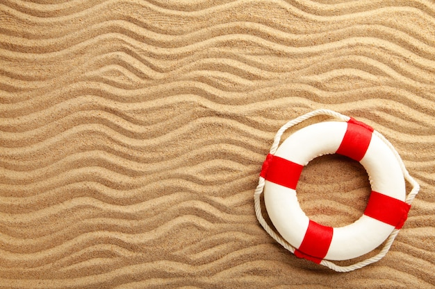 Red-white lifebuoy on sand. summer concept with copy space
