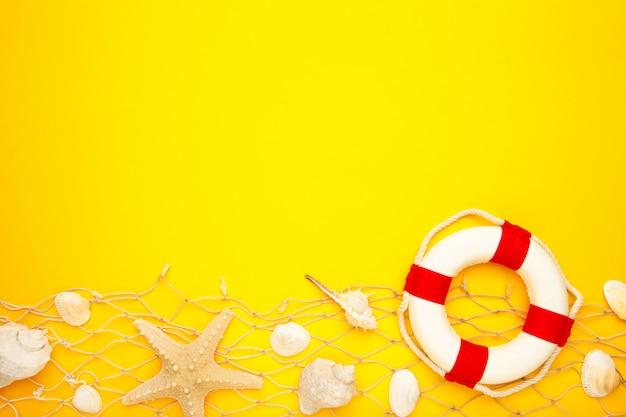 Красно-белый спасательный круг с песком и ракушками на синем