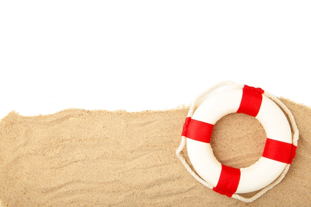 Red-white lifebuoy with sand isolated