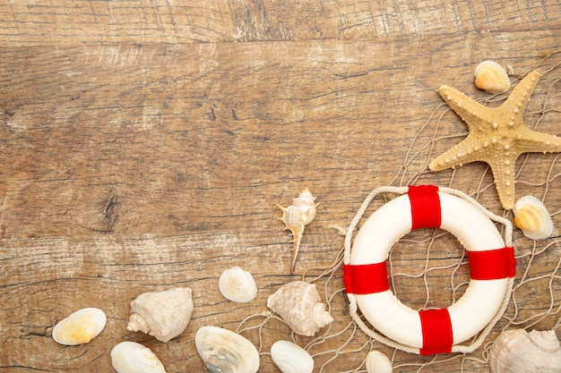 Red-white lifebuoy with sand and seashells on brown