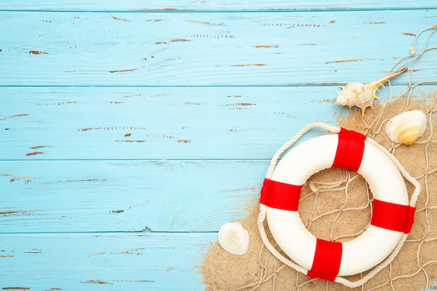 Red-white lifebuoy with seashells on a wooden background