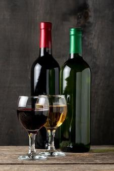 Uno rosso e bianco in bicchieri accanto a bottiglie