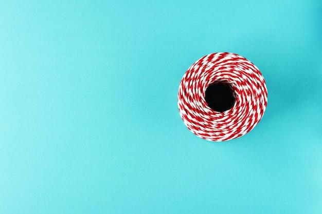 赤白青の背景にクリスマスロープを梱包
