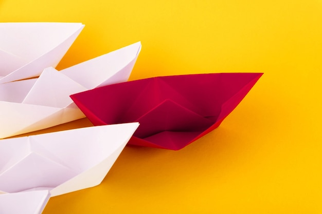 Red and white paper boats on a yellow background. leadership concept. copy space.