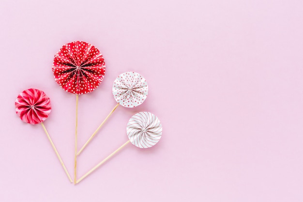 Red and white paper fan with wooden stick on pink background for party decoration