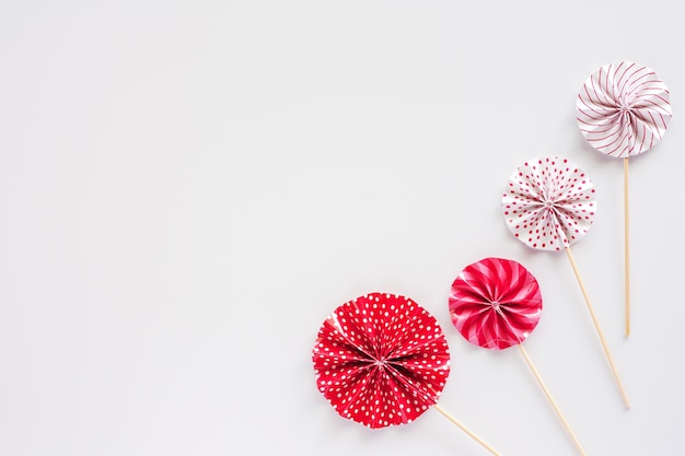 Red and white paper fan with wooden stick on white background for party decoration