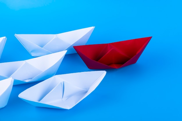 Red, white paper ship on a blue background. leader concept. copy space.