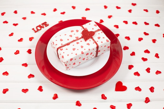 Red and white plate, gift in a box and festive decor heart shaped. valentines day concept.