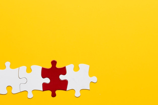 Red and white puzzle piece with yellow copy space background