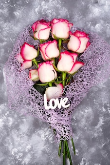 赤い白い花の花束とレタリング石テーブルの愛。