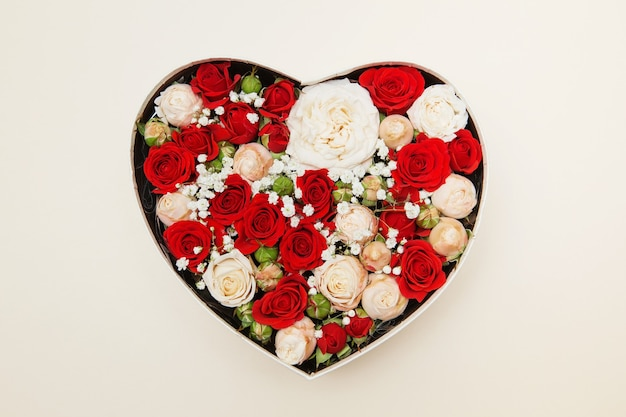 Red and white roses in a white box in the form of a heart